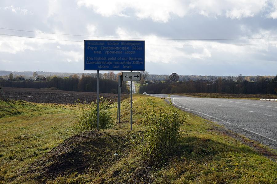widok drogi od strony wsi Wiertniki, po lewej stronie tablica informująca o szczycie