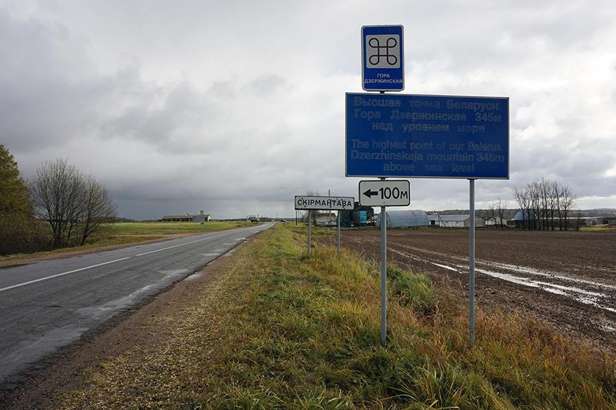 widok drogi od strony wsi Wołma , po prawej stronie tablica informująca o szczycie. W tle tablica Skirmuntowo