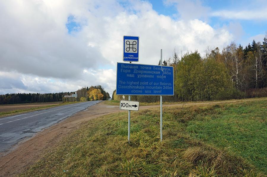 widok drogi od strony wsi Skirmuntowo, po prawej stronie tablica informująca o szczycie