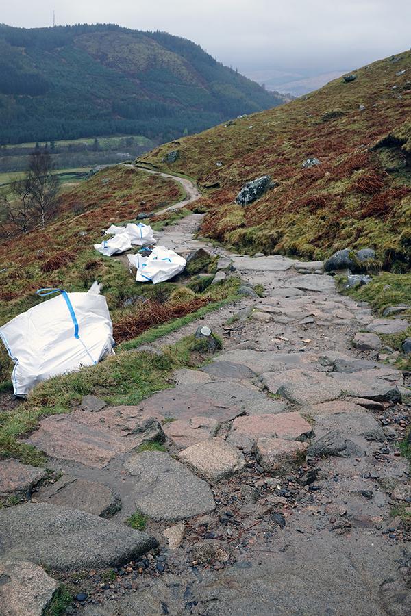 droga na szczyt. Na drodze znajdują się torby z kamieniami do naprawy szlaku