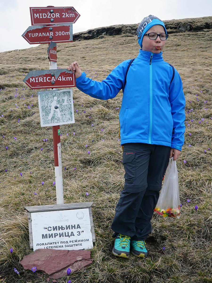 drogowskazy informujące o celu trekkingu, obok Kajetan i jego torba żelków na drogę