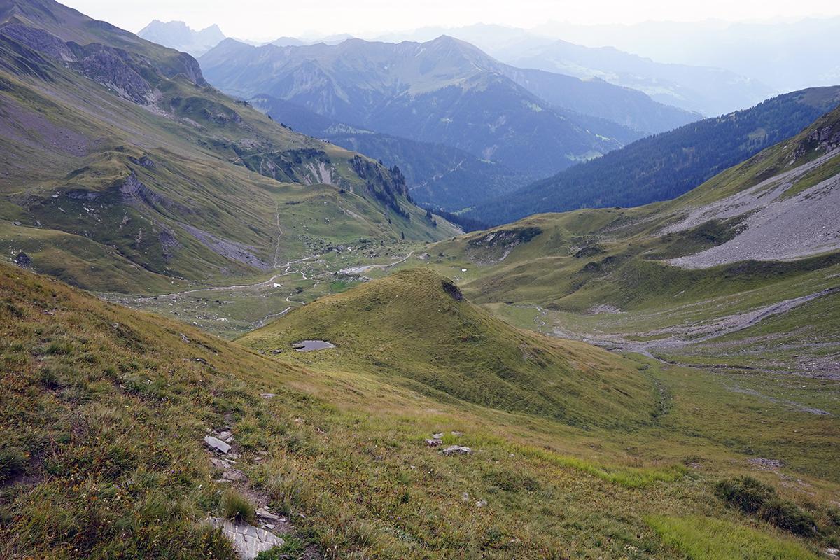 widok ze wzniesienia prowadzącego na grań, w dole droga skręcająca w prawo do opisywanych tuneli